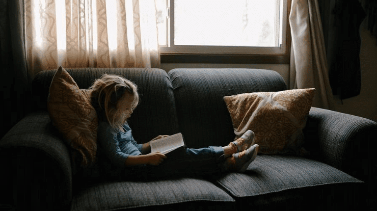 Little girls reading with soundproof curtains blocking noise