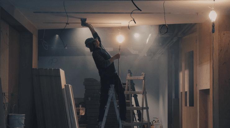 Man installing plasterboard