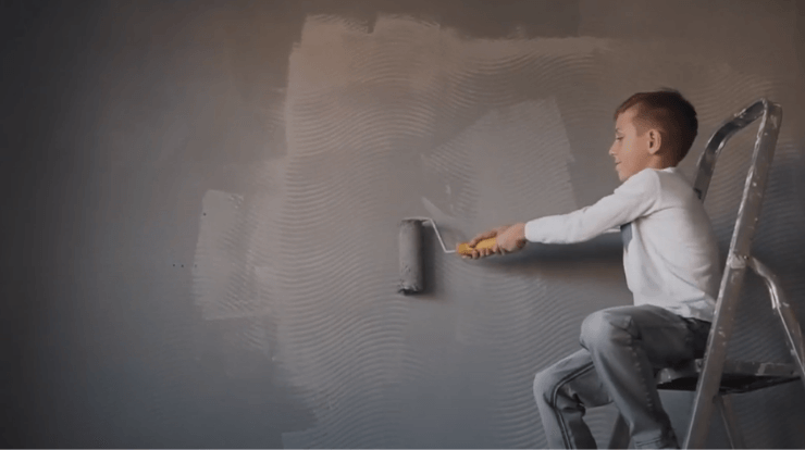 A boy applying soundproof paint on a wall